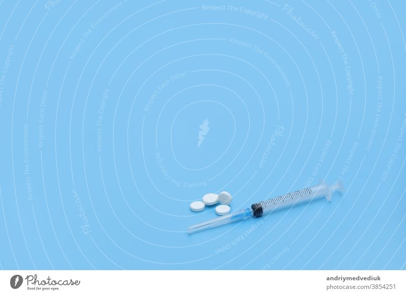 Spritze und weiße Pillen auf blauem Hintergrund. Platz für Ihren Text. Medizinischer Hintergrund. medizinisch Stethoskop Krankheit Gesundheit Kur Verschreibung