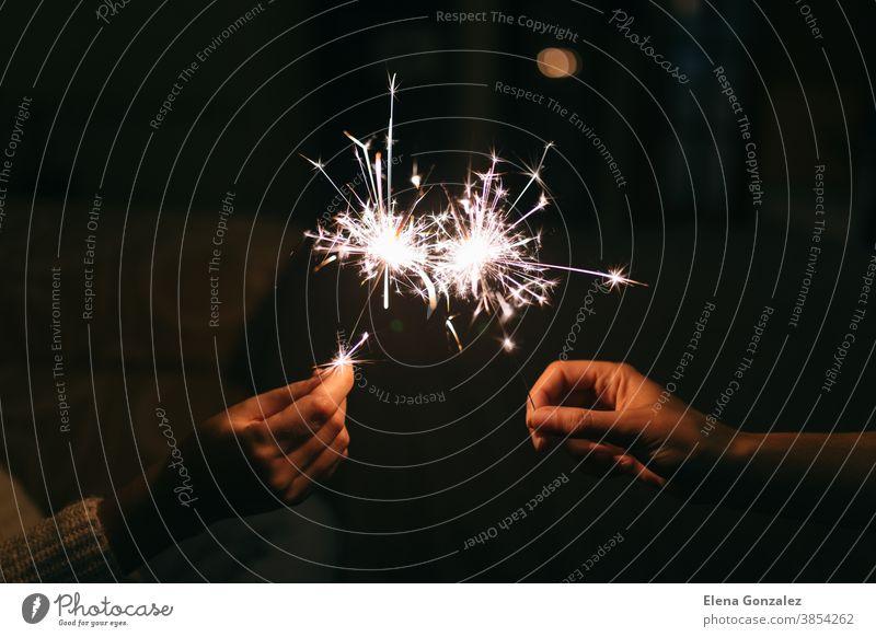 Brennende Wunderkerze zum Jahreswechsel. Bengalisches Licht wird in kleine Funken gestreut. Feiern Weihnachten und Neujahr 2021 Frohe Weihnachten Hintergründe