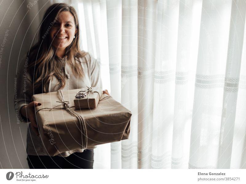 Junge Frau hält in den Händen gestapelte Weihnachtsgeschenkkartons aus Bastelpapier mit Wacholder. Konzept der Weihnachtsgeschenke. Weihnachten