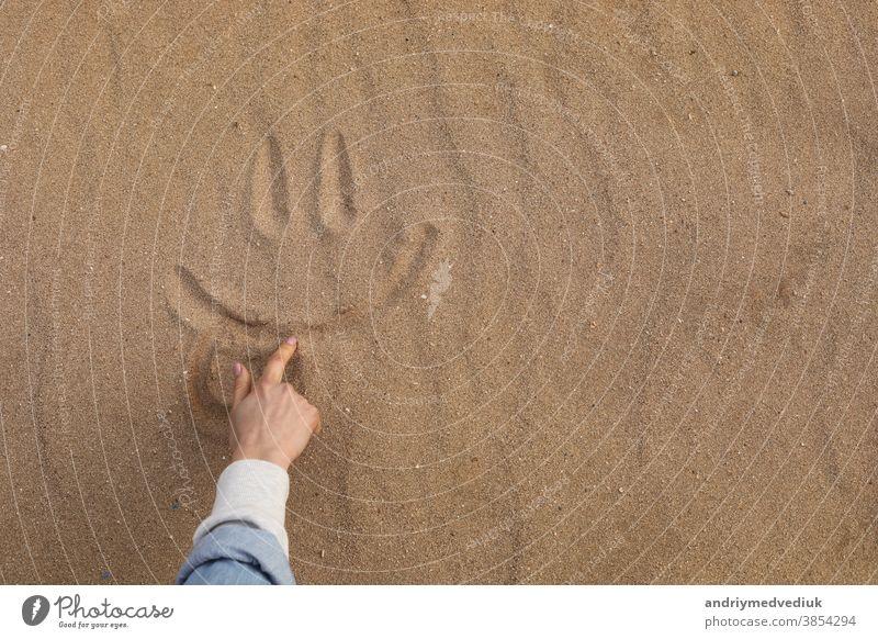 Ein schönes süßes Lächeln im Wüstensand von Hand zeichnen - Hintergrund Fuß Sand Feiertag Spaß Textur Gesicht Strand Symbol Sonne Freude Lifestyle sonniger Tag