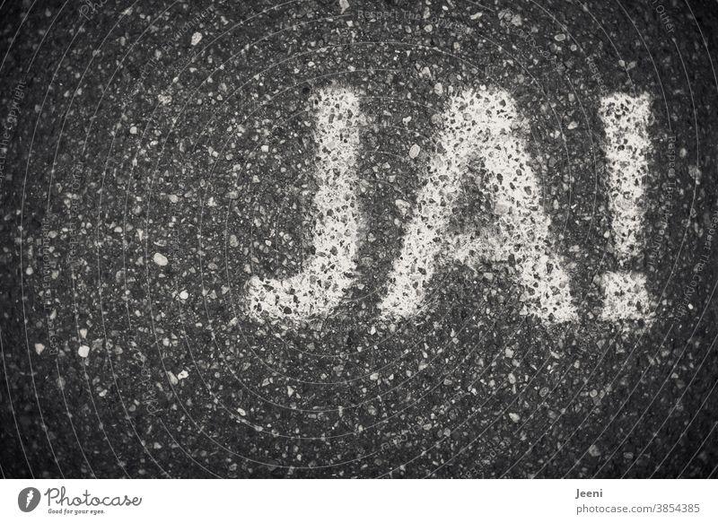 Das Wort JA auf einen Weg gemalt - Straßenmalerei Ja Jasager Zustimmung Entscheidung Schriftzeichen Wahlen wählen heiraten Demokratie Entschlossenheit Hochzeit