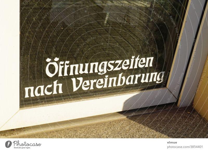 """""""Öffnungszeiten nach Vereinbarung"""" steht in weißer Druckschrift im unteren Teil einer Glastür zu einem Geschäft. Ladentür Ausnahmesituation geschlossen"""