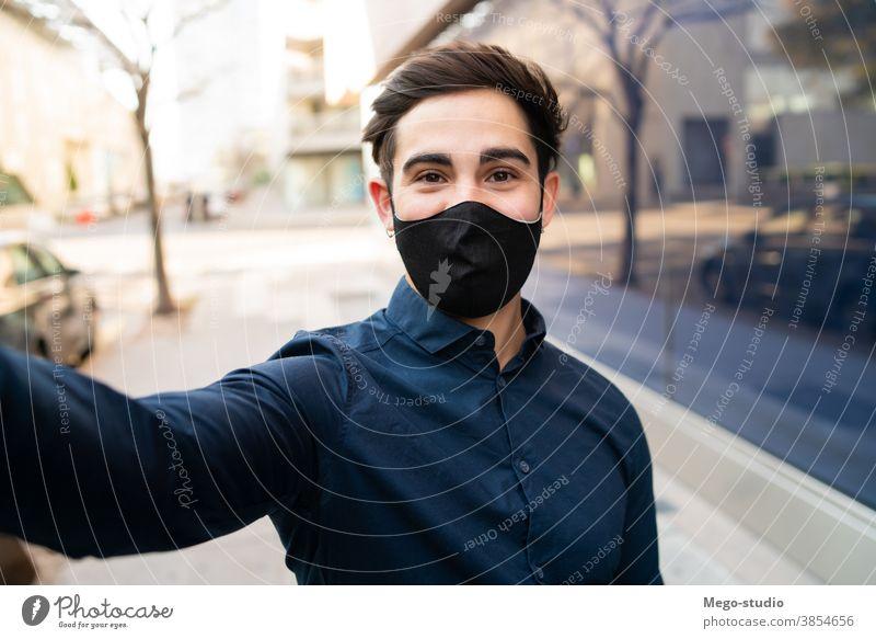 Porträt eines jungen Mannes, der ein Selfie im Freien macht. Gesicht Mundschutz covid-19 außerhalb normal neu Lifestyle Selfie machen Leben lässig Stil tragend