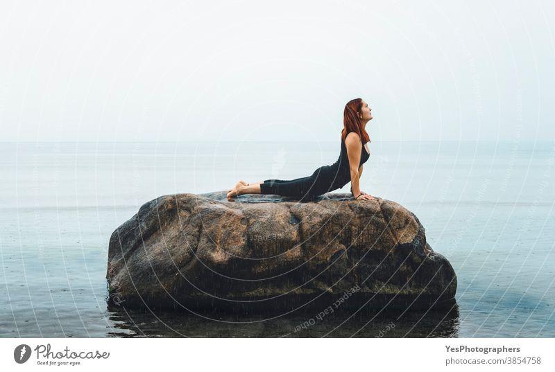 Junge Frau, die Yoga praktiziert, auf See, im Regen. Rothaariges Mädchen meditiert auf einem Felsen in der Ostsee, Deutschland 20s Iyengar-Yoga Erwachsener