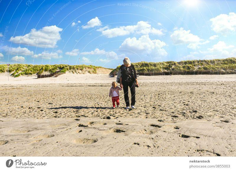 Großmutter und Kleinkind gehen am Sandstrand spazieren Strand Kind Vorderansicht laufen Spaziergang Totale Wegsehen Kindheit Kaukasier Düne sonnig gutes Wetter