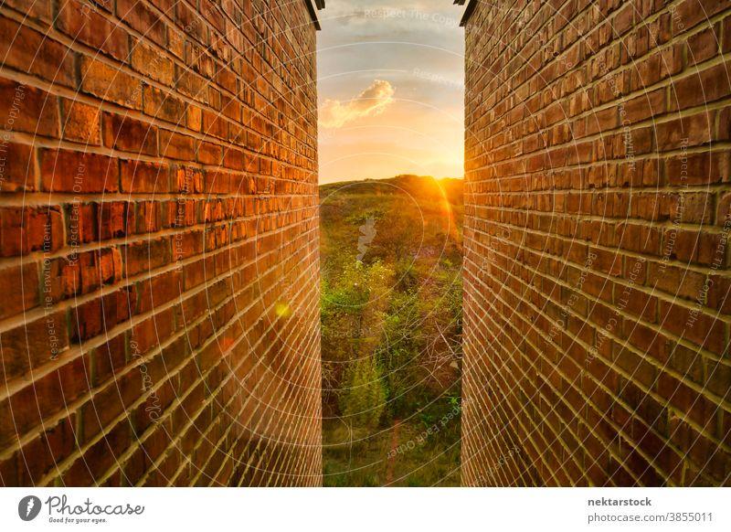 Goldener Sonnenaufgang und Landschaft zwischen Backsteinmauern Wand Baustein eng golden Eröffnung Licht am Ende des Tunnels Gabellandschaft Konzept Hoffnung