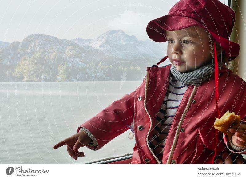 Kleinkind schaut weg und zeigt auf Berge und Seen im Hintergrund Kind 2 Jahre alt Kaukasier Porträt im Innenbereich niedlich Kindheit klein Mantel Hut Zeigen