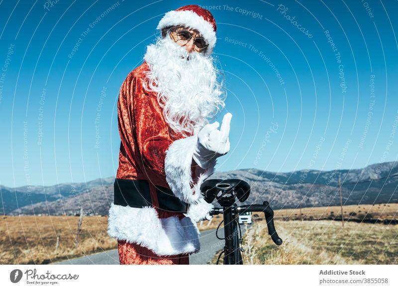 Unhöflicher Weihnachtsmann zeigt Mittelfinger ficken unverschämt gestikulieren Fahrrad Straße Weihnachtsmütze auflehnen expressiv männlich stehen ländlich