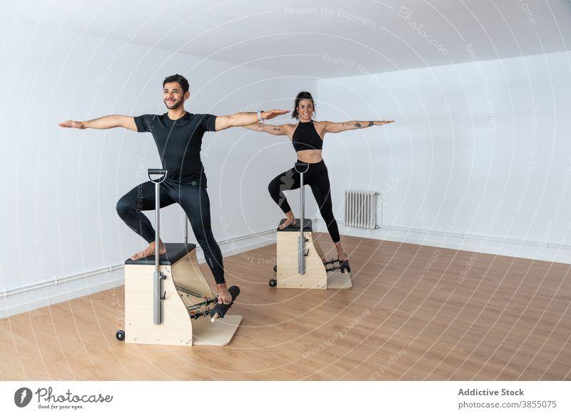 Sportler bei Übungen während des Pilates-Trainings Stuhl üben Sportlerin Fitnessstudio passen Barfuß hell Gesundheit schlank Athlet Energie Kraft Bestimmen Sie