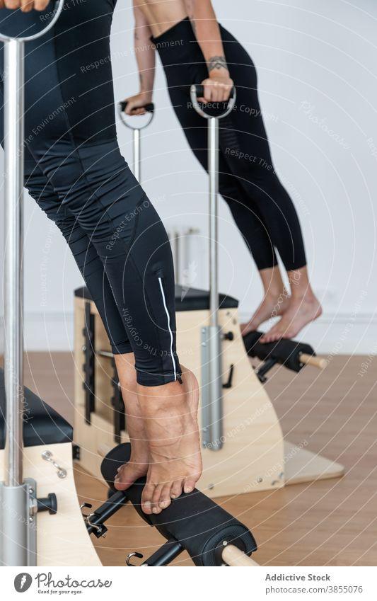 Crop-Sportler bei Übungen auf Pilates-Stühlen Stuhl üben Training Sportlerin Gleichgewicht Fitnessstudio Gesundheit Athlet Wellness passen Sportbekleidung