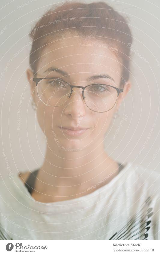Kluge Frau schaut in die Kamera Vorschein Grinsen klug jung Porträt Brille lässig selbstbewusst Individualität clever modern Model Accessoire intelligent