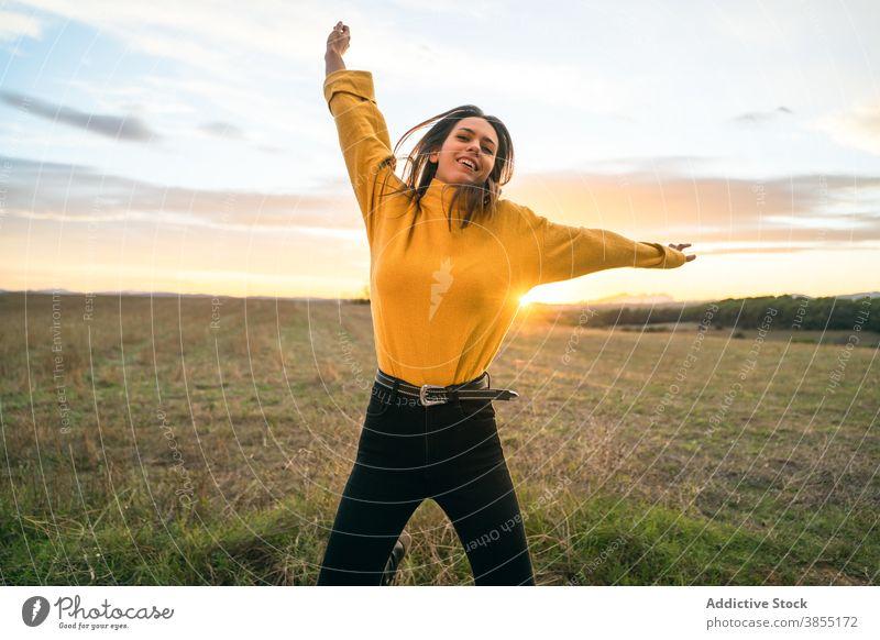 Fröhliche Frau springt im Feld bei Sonnenuntergang springen sorgenfrei Freiheit genießen Lächeln Moment Landschaft Outfit lässig Wiese ländlich Gegend aktiv