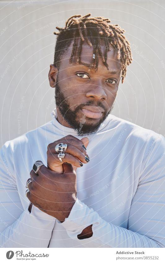 Stilvoller schwarzer Mann mit ungewöhnlichem Aussehen Rastalocken Vorschein Maniküre ausgefallen Frisur Ring Hipster Porträt männlich ethnisch Afroamerikaner