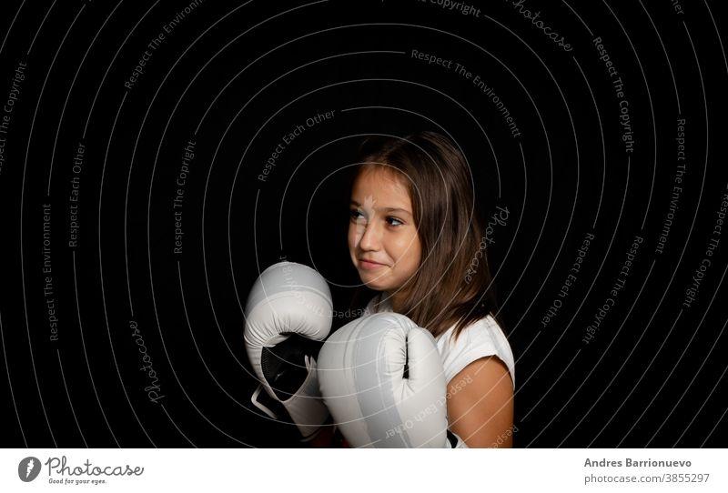 Hübsches kleines Mädchen mit Boxhandschuhen posiert lustig auf schwarzem Hintergrund sportlich gestikulieren Training passen Gesundheit Dame hübsch tragend Frau