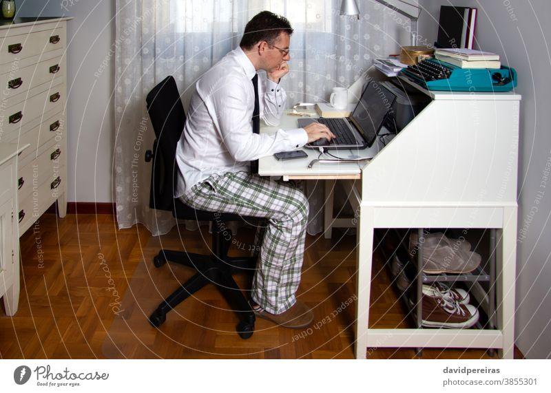 Mann bei der Telearbeit mit Hemd, Krawatte und Pyjamahose von zu Hause aus arbeiten Coronavirus Seuche Quarantäne soziale Distanzierung Laptop Internet