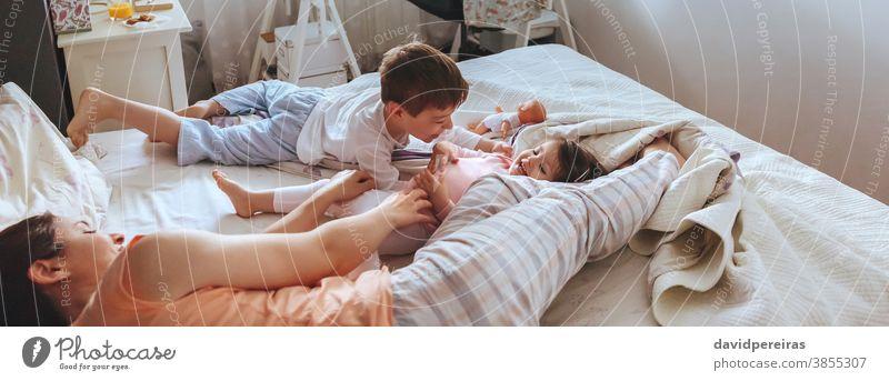 Entspannte Mutter und Söhne spielen über dem Bett. covid-19 Einsperrung Familie Kind Spielen panoramisch Panorama Lachen heiter Lächeln Fröhlichkeit Coronavirus