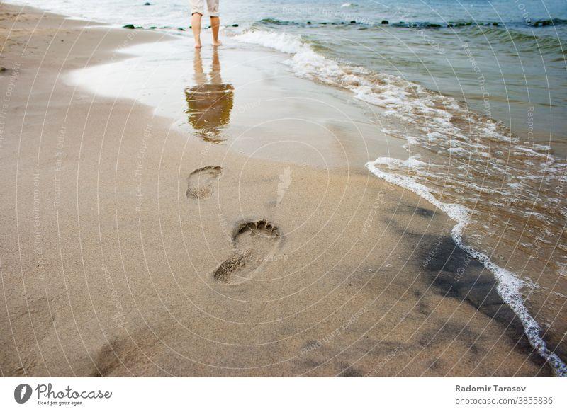 Fußabdrücke von Frauen am Meeresufer Bein Sand Wasser MEER Sommer Spaziergang Strand Küste winken Barfuß Lifestyle Person jung sich[Akk] entspannen Menschen