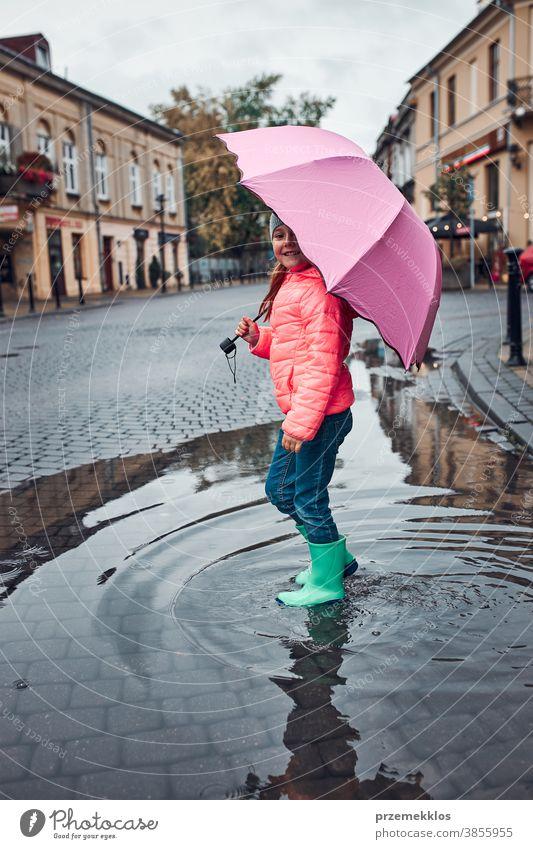 Kleines Mädchen mit großem rosa Regenschirm in der Hand geht an einem verregneten, düsteren Herbsttag durch die Innenstadt im Freien wenig saisonbedingt fallen