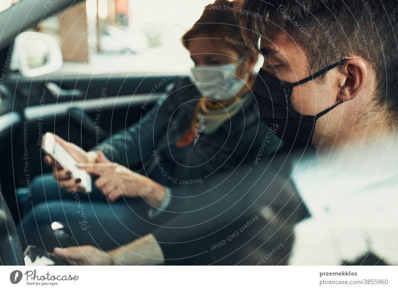 Mann und Frau sitzen in einem Auto und benutzen Smartphones und tragen die Gesichtsmasken, um eine Virusinfektion zu vermeiden Kaukasier covid-19 Lifestyle