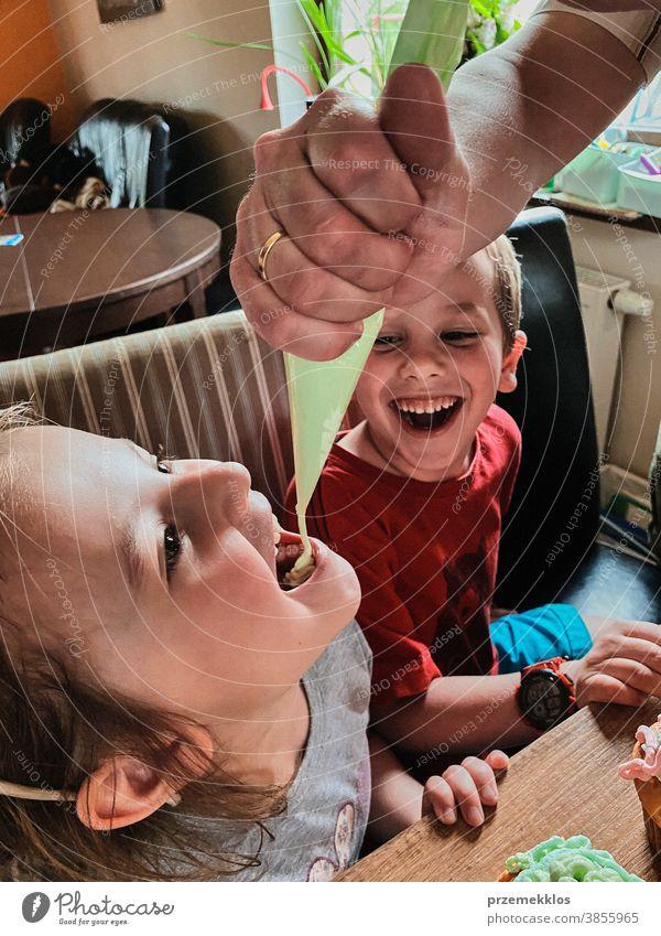 Kind isst Schlagsahne, die direkt aus der Tüte gepresst wurde Kinder backen Cupcake dekorierend Keks vorbereitend Essen zubereiten Familie heimisch Muffin