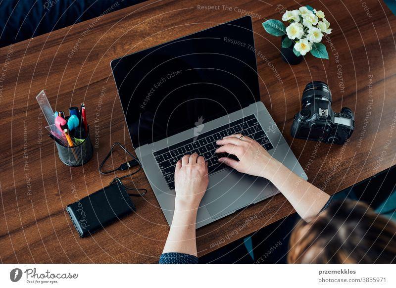 Fotografin, die an Fotos auf Laptop und Kamera arbeitet Unternehmer Kaukasier Büro kreativ Fotografie Person Frau Notebook modern im Innenbereich Tisch klug