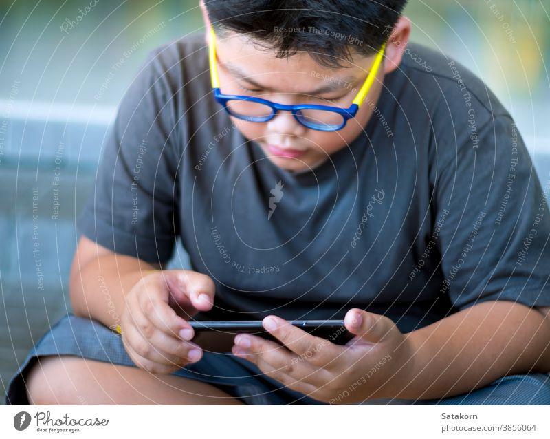 Asiatischer Junge hat beim Spielen auf Smartphone ein ernstes Gesicht Kind Telefon spielen Schweiß asiatisch Kinder Hand Brille Technik & Technologie klug jung