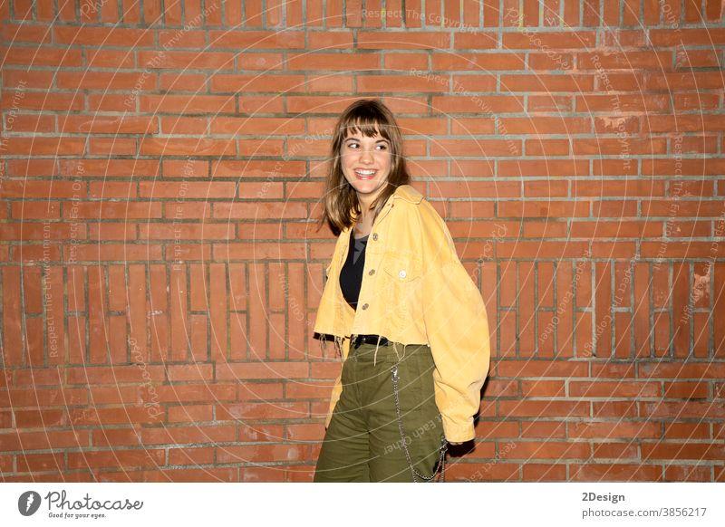 Hübsche junge Frau steht nachts an einer alten Ziegelmauer in der Stadt Stehen attraktiv Lächeln Glück Wand Baustein Freizeitkleidung Person schön Lifestyle