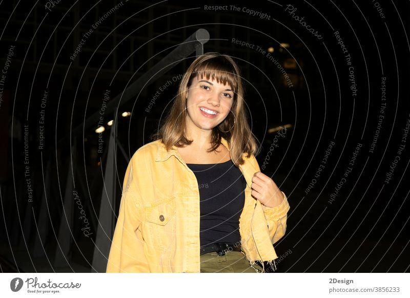 Junges, hübsches Mädchen sitzt nachts auf einer Bank in einem öffentlichen Stadtpark und schaut in die Kamera jung Frau Nacht Sitzen 1 schön attraktiv Glück
