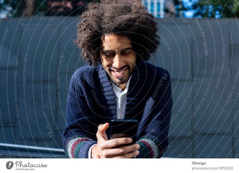 Lächelnder Afroamerikaner schreibt am Telefon SMS an Freunde. Mann 1 Afro-Look Mobile Glück männlich Technik & Technologie Handy Nachricht schwarz Typ
