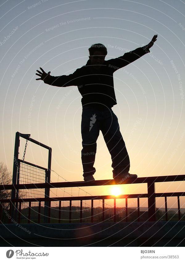 Poser im Untergang Mensch Mann Himmel schwarz Zufriedenheit Tür Typ Geländer Gleichgewicht Kerl Drahtzaun