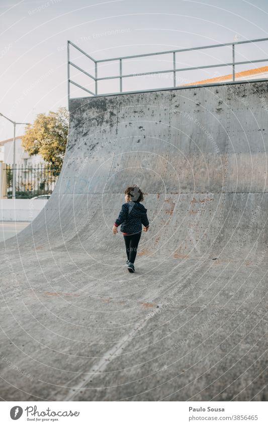 Rückansicht eines im Skatepark spielenden Kindes Skateboarding Skateplatz Halfpipe Kindheit Kinderspiel Park Herbst authentisch copyspace Textfreiraum