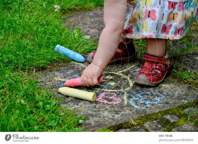 Enkelkind bemalt einen alten Gartenweg farblich passend zum Kleidchen....... Kind kindlich Sommertag Steinplatten zeichnen Buntstifte blau rot Gras Grünfläche