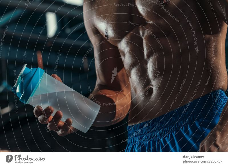 Muskulöser Mann mit Proteindrink im Shaker Athlet sportlich Bizeps Körper Bodybuilder Bodybuilding Truhe Diät trinken passen Fitness Typ Fitnessstudio