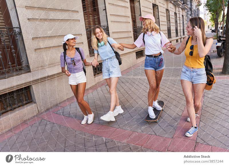 Glücklich teen Freundinnen zu Fuß auf der Straße der Stadt Menschengruppe Teenager Spaß haben Zusammensein heiter Skateboard Spaziergang urban