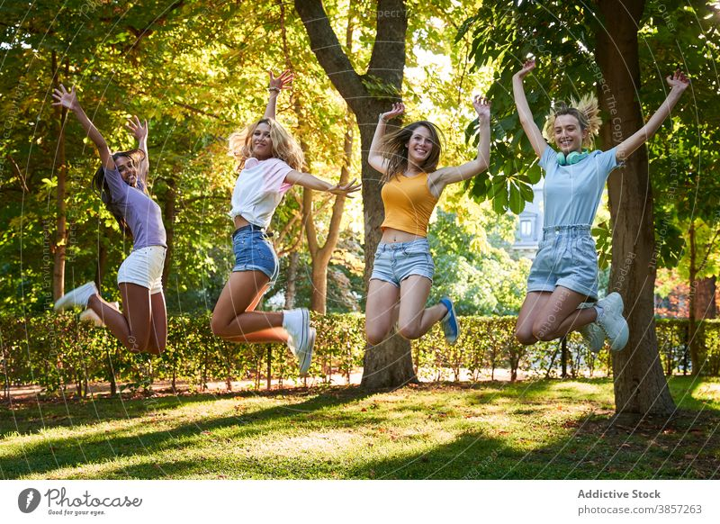 Gruppe von verschiedenen Teenager-Freundinnen springen hoch im Park Spaß haben Sommer Glück heiter Zusammensein Frauen rassenübergreifend multiethnisch