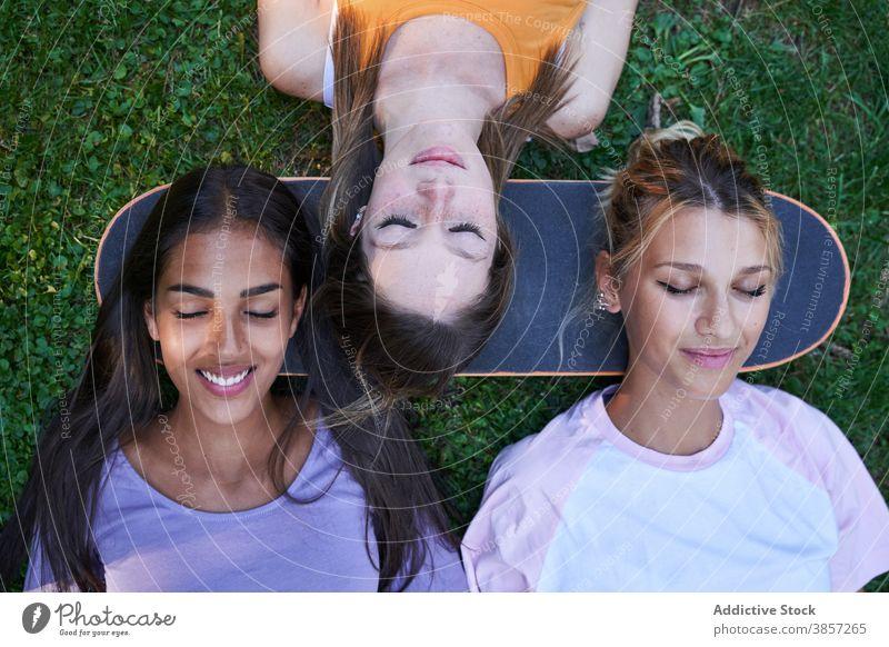 Junge Frauen mit Skateboard liegend auf grünem Gras Freundin Park Kälte Lügen Sommer Glück heiter Zusammensein ruhen Teenager rassenübergreifend multiethnisch