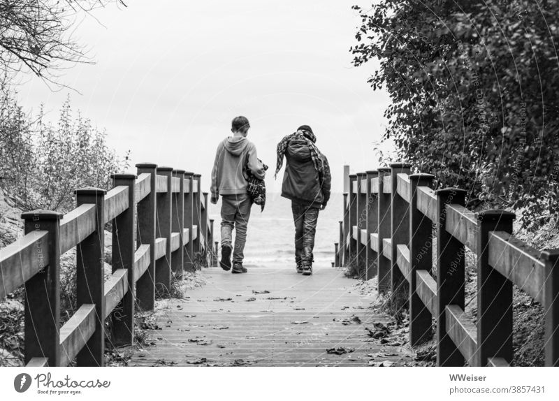 Zwei Freunde brechen zu einem Strandspaziergang auf, gegen jedes Wetter gewappnet Jungs Kinder Jugendliche Düne Strandaufgang Wind Regen Herbst kalt windig