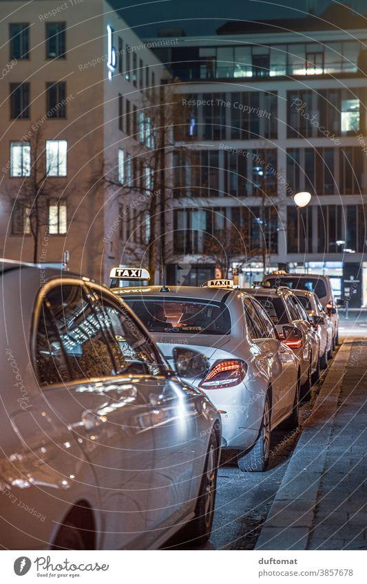 Taxis die auf Kundschaft warten Taxifahrer Taxistand Nacht Licht München Berufsverkehr wartend aufgereiht Abend Nachtleben Straße Warteschlange Kreuzung