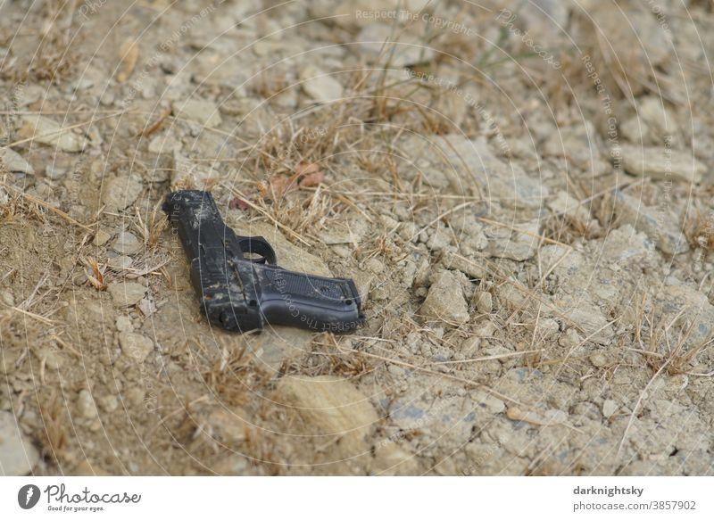 Schwarze Pistole als zurück gelassene gefährliche Waffe an einem Tatort des Verbrechens. Halbautomatikwaffe Automatikwaffe schwarz Bedrohung verloren