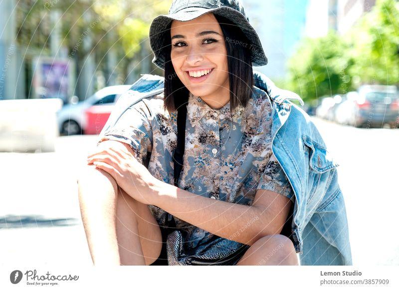 Porträt einer brünetten Latina-Frau mit Hut, die in die Kamera blickt und ihren Arm in einer Hand hält lateinamerikanerin städtischer Hintergrund Person