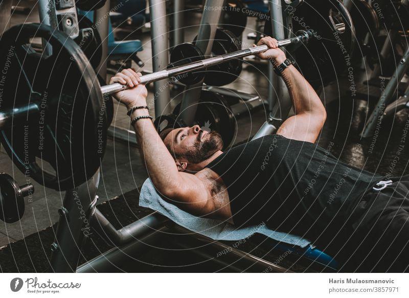 Mann hebt Gewichte in der Turnhalle abdominal Bauchmuskeln Erwachsener Athlet sportlich attraktiver Mann Bizeps Körper Bodybuilding Bodybuilder Kaukasier Truhe