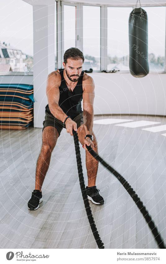 Mann trainiert mit Seilen in der Turnhalle abdominal Bauchmuskeln Erwachsener Athlet sportlich attraktiver Mann Bizeps Bodybuilding Kaukasier Truhe