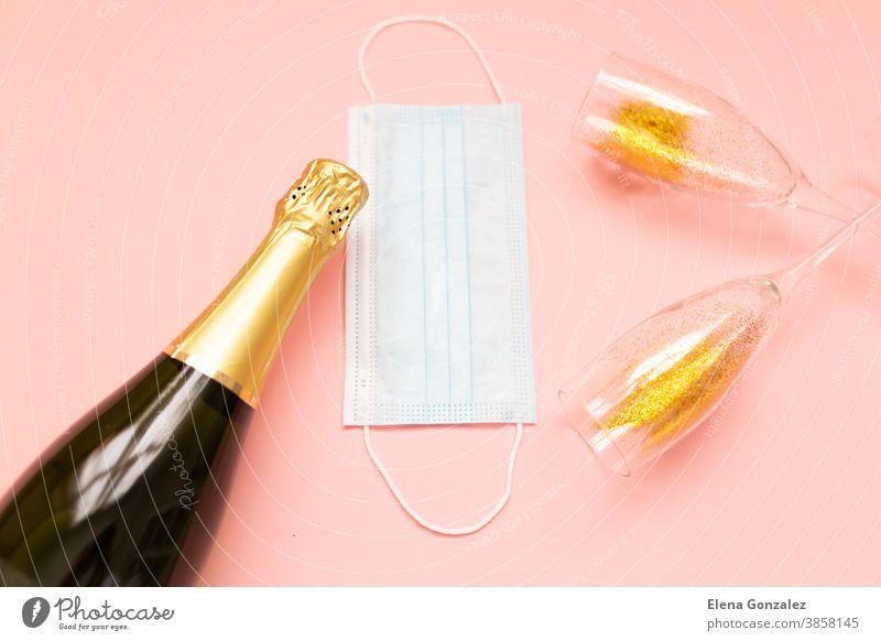 Flasche mit Champagner-Gesichtsmaske und Gläsern mit Goldglitzer auf rosa Hintergrund. Party-Dekoration. Weihnachts-, Geburtstags- oder Hochzeitskonzept. Flachgelegt. Festlich, Getränk. Neujahr 2021-Feier.