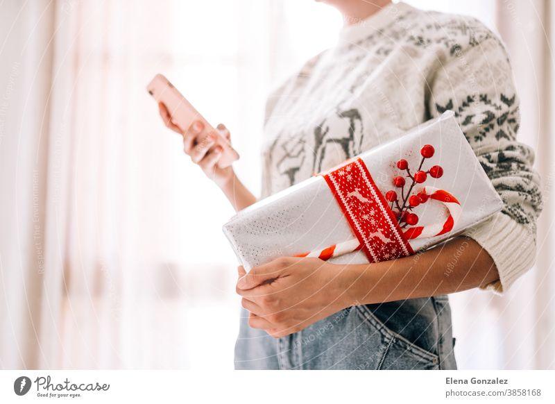 Junge unerkennbare Frau, die ihr Mobiltelefon in einer Geschenkbox aus Metallpapier mit rotem Zwirn und Süßigkeiten in der Hand hält. Weihnachts-Silvester-Geschenk.