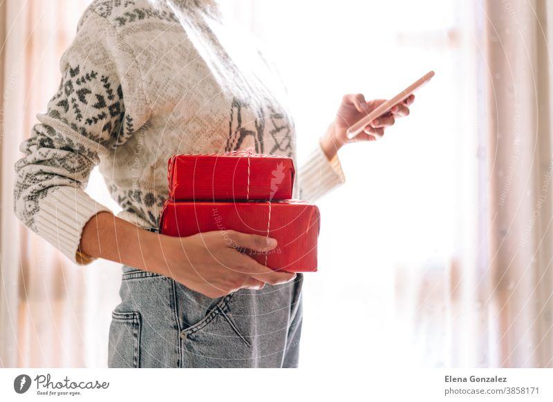 Junge unkenntlich beim Beobachten ihres Mobiltelefons Frau beim Beobachten ihres Mobiltelefons hält rote Geschenkkartons. Weihnachts-Silvester-Geschenk.