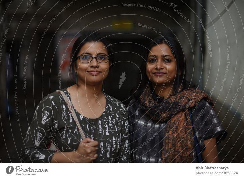 Porträt von zwei indisch-bengalischen brünetten Frauen/Freunden/Schwestern, die in einer Straße in einer Gasse in Bengalen stehen. Indischer Lebensstil