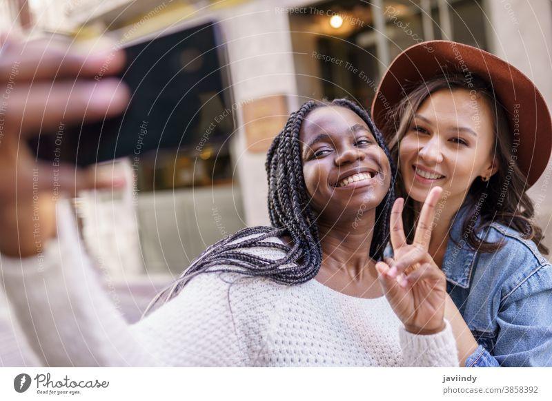 Zwei schöne multiethnische Frauen, die Selbstgefälligkeit und Grimassen schneiden Selfie Smartphone Lifestyle jung Mädchen Lächeln Straße Glück lässig urban