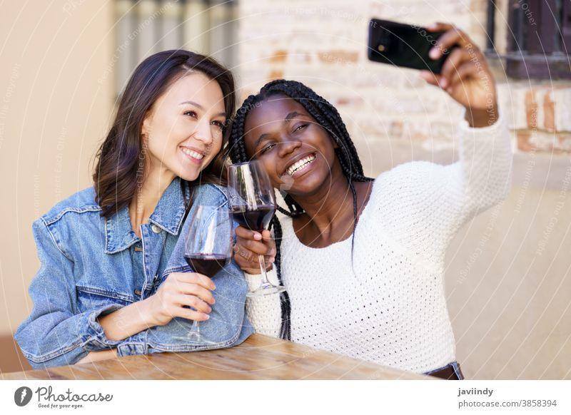 Zwei Frauen, die bei einem Glas Wein ein Selfie mit einem Smartphone machen. Bar im Freien rassenübergreifend Fröhlichkeit Mädchen Freundschaft Glück Lächeln
