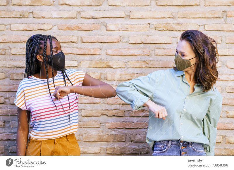 Multiethnische junge Frauen mit Masken, die einander mit den Ellbogen grüßen Begrüßung Menschen sozial Distanzierung Mundschutz Pandemie Virus Coronavirus
