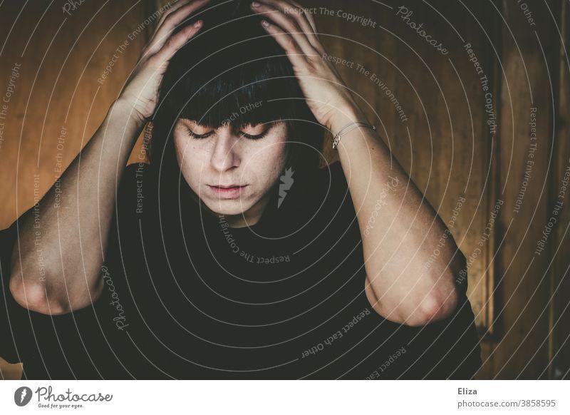 Portrait einer Frau, die nachdenklich, niedergeschlagen dasitzt und den Kopf in den Händen hält traurig Hände am Kopf depressiv verzweifelt betrübt Trübsal